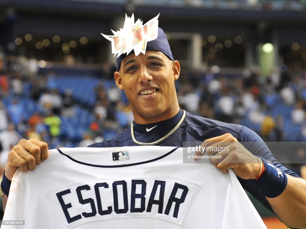 Infielder Yunel Escobar of the Tampa Bay Rays hold his jersey for a fan give away after play against the Baltimore Orioles September 23, 2013 at Tropicana Field in St. Petersburg, Florida. The Rays won 5 - 4.