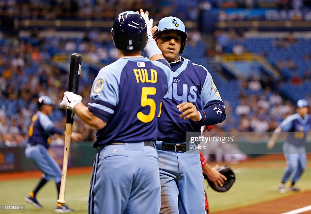 Infielder <a gi-track='captionPersonalityLinkClicked' href=/galleries/search?phrase=Yunel+Escobar&family=editorial&specificpeople=757358 ng-click='$event.stopPropagation()'>Yunel Escobar</a> #11 of the Tampa Bay Rays is congratulated by Sam Fuld #5 after scoring a second inning run against the Chicago White Sox at Tropicana Field on July 6, 2013 in St. Petersburg, Florida.