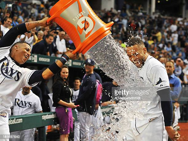 Infielder Yunel Escobar of the Tampa Bay Rays showers pinch hitter James Loney after play against the Baltimore Orioles September 23 2013 at...