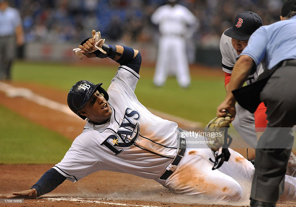 Infielder <a gi-track='captionPersonalityLinkClicked' href=/galleries/search?phrase=Yunel+Escobar&family=editorial&specificpeople=757358 ng-click='$event.stopPropagation()'>Yunel Escobar</a> #11 of the Tampa Bay Rays slides for a run against the Boston Red Sox June 10, 2013 at Tropicana Field in St. Petersburg, Florida. Boston won 10 - 8 in 14 innings.