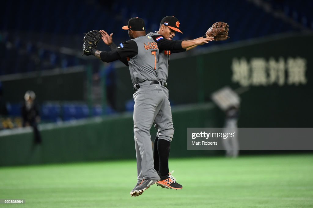 Infielder Yurendell de Caster (L) #7 and Infielder Xander Bogaerts (R) #1 of the Netherlands celebrate their 12-2 victory in the World Baseball Classic Pool E Game Three between Netherlands and Israel at the Tokyo Dome on March 13, 2017 in Tokyo, Japan.