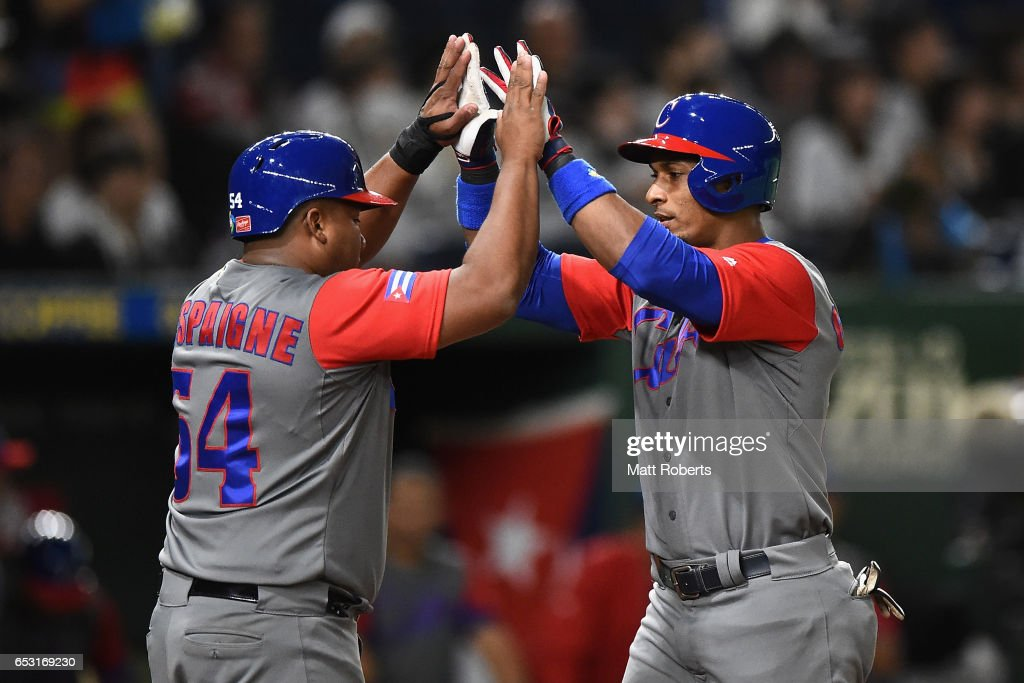 Infielder Yurisbel Gracial (R) #47 of Cuba high fives with Outfielder Alfredo Despaigne #54 after hitting a two run homerun in the top of the second inning during the World Baseball Classic Pool E Game Four between Cuba and Japan at the Tokyo Dome on March 14, 2017 in Tokyo, Japan.