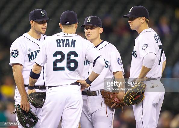 Infielders Alex Liddi Brendan Ryan Kyle Seager and Justin Smoak of the Seattle Mariners meet during a game against the Texas Rangers at Safeco Field...