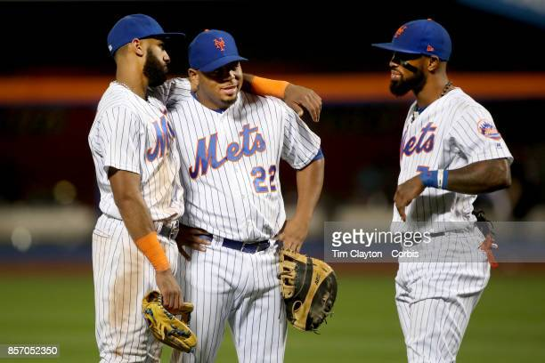 Infielders Amed Rosario of the New York Mets Dominic Smith of the New York Mets and Jose Reyes of the New York Mets talk during a pitching change...