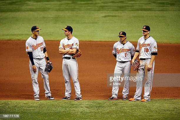 Infielders Manny Machado JJ Hardy Brian Roberts and Chris Davis of the Baltimore Orioles await a pitching change against the Tampa Bay Rays during...