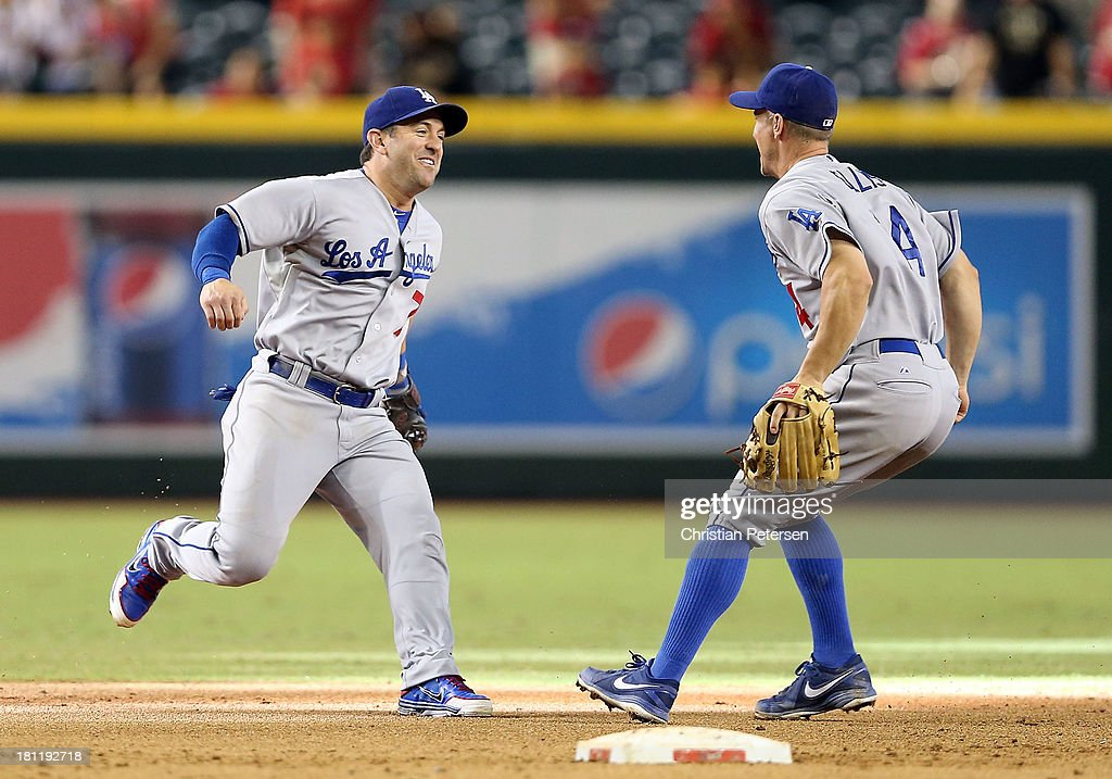 Infielders Nick Punto #7 and Mark Ellis #14 of he Los Angeles Dodgers celebrate after defeating the Arizona Diamondbacks to clinch the National League West title and a postseason berth at Chase Field on September 19, 2013 in Phoenix, Arizona.