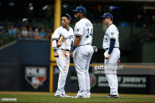 Infielders Orlando Arcia Jesus Aguilar and Neil Walker of the Milwaukee Brewers wait during a play review during the sixth inning against the Miami...