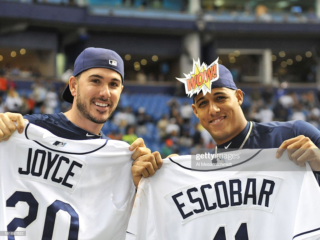 Infielders Yunel Escobar #11 and Matt Joyce #20 of the Tampa Bay Rays hold jerseys for a fan give away after play against the Baltimore Orioles September 23, 2013 at Tropicana Field in St. Petersburg, Florida. The Rays won 5 - 4.