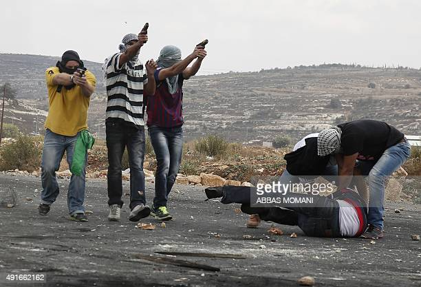 Infiltrated members of the Israeli security forces detain a Palestinian stone thrower and fire towards fellow protesters during clashes in Beit El on...
