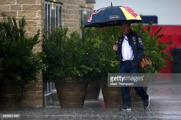 Infiniti Red Bull Racing Team Consultant Dr Helmut Marko uses an umbrella to shelter from the rain as he leaves the paddock after practice for the...