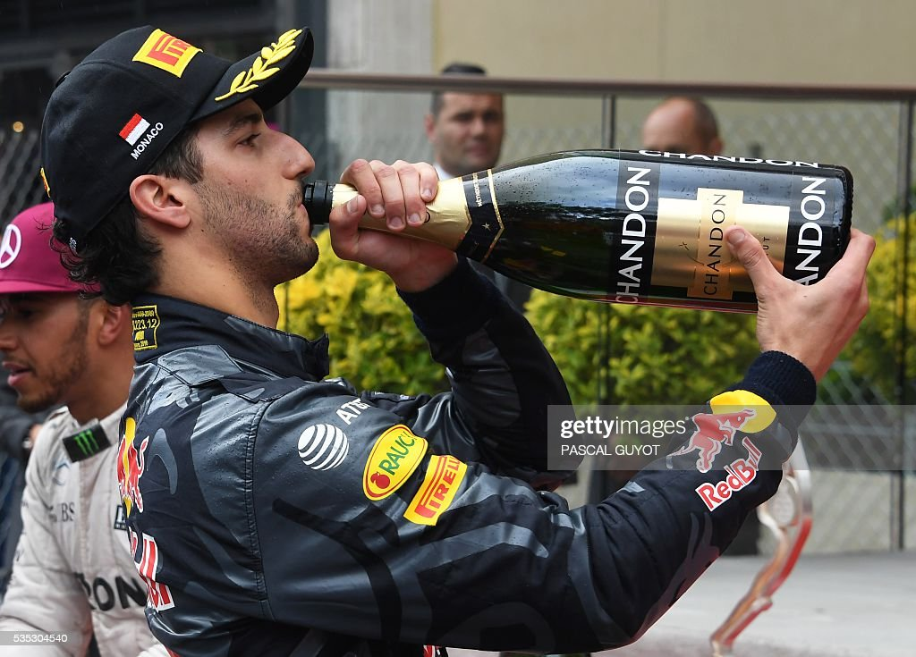 Infiniti Red Bull Racing's Australian driver Daniel Ricciardo drinks champagne as he celebrates on the podium at the Monaco street circuit, on May 29, 2016 in Monaco, after the Monaco Formula 1 Grand Prix. / AFP / PASCAL