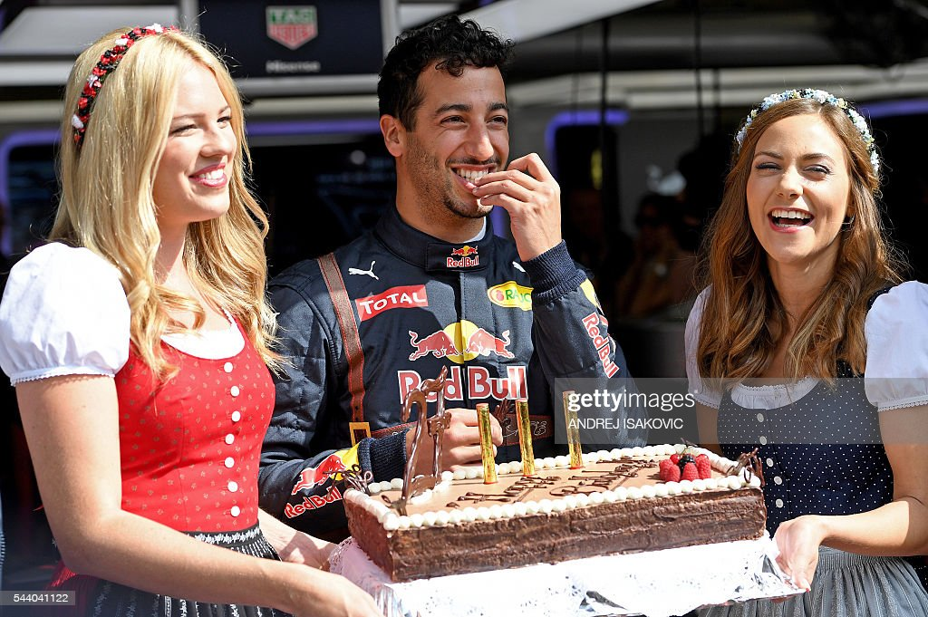 Infiniti Red Bull Racing's Australian driver Daniel Ricciardo (C) poses with his 27th birthday cake in the pit lane before the first practice session of the Formula One Grand Prix of Austria at the Red Bull Ring in Spielberg, Austria on July 1, 2016. / AFP / ANDREJ