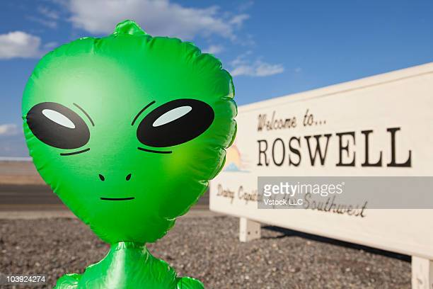 Inflatable alien with Welcome to Roswell sign in background