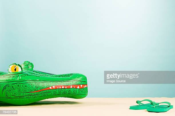 Inflatable crocodile and flip flops