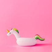 Inflatable unicorn pool toy on pastel pink background. Minimal summer concept.