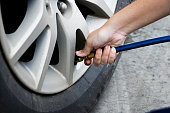 inflating tire and checking air pressure in service station.Filling air into a car tire at service center