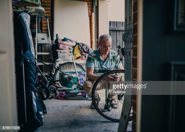 Inflating Tire of Bicycle in His Garage