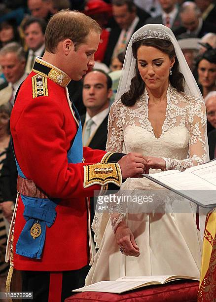 INFOBritain's Prince William puts a ring fashioned from a nugget of Welsh gold on ther finger of Kate Duchess of Cambridge in front of the Archbishop...