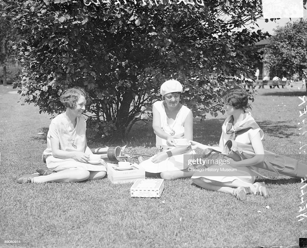Informal fulllength portrait of Bertha Fields Nelli Alcher and Edna Johnson sitting in front of a large bush on a lawn in Chicago Illinois 1929...