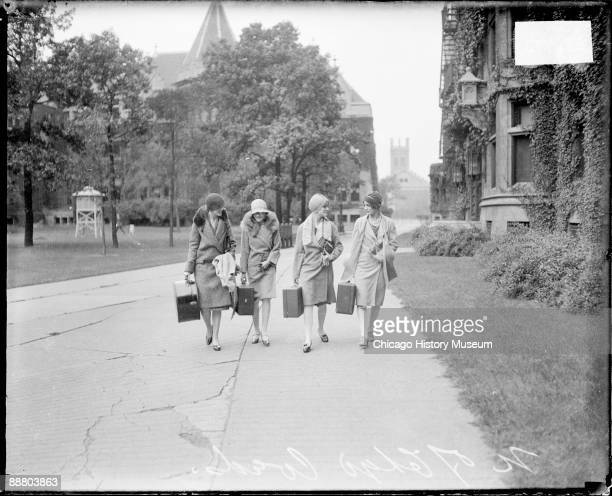 Informal fulllength portrait of four young women carrying rectangular cases walking in the Social Sciences quadrangle on the University of Chicago...