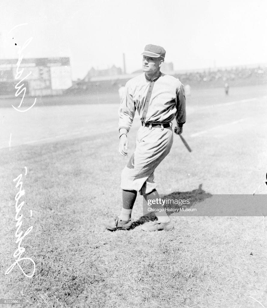 Informal fulllength portrait of pitcher Walter Johnson of the American League's Washington Senators following through after swinging a baseball bat...