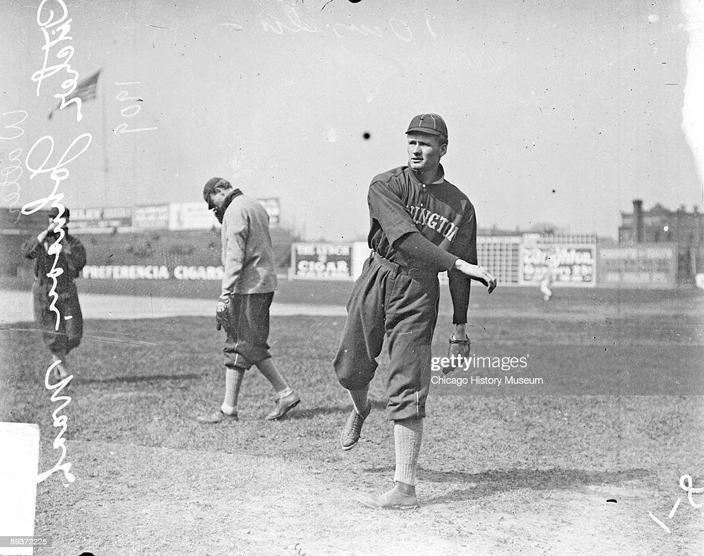 Informal fulllength portrait of pitcher Walter Johnson of the American League's Washington baseball team following through after throwing a baseball...