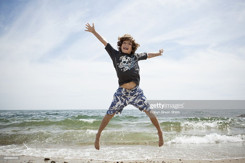 Informal portrait of jumping boy on beach at Falmouth, Massachusetts, USA : Stock Photo
