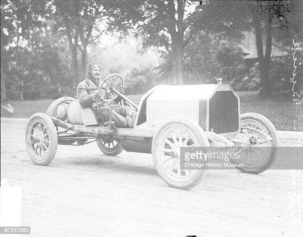 Informal portrait of L Chevrolet sitting in a Buick automobile parked in the street in Crown Point Indiana during the Cobe Cup Race 1909 A building...