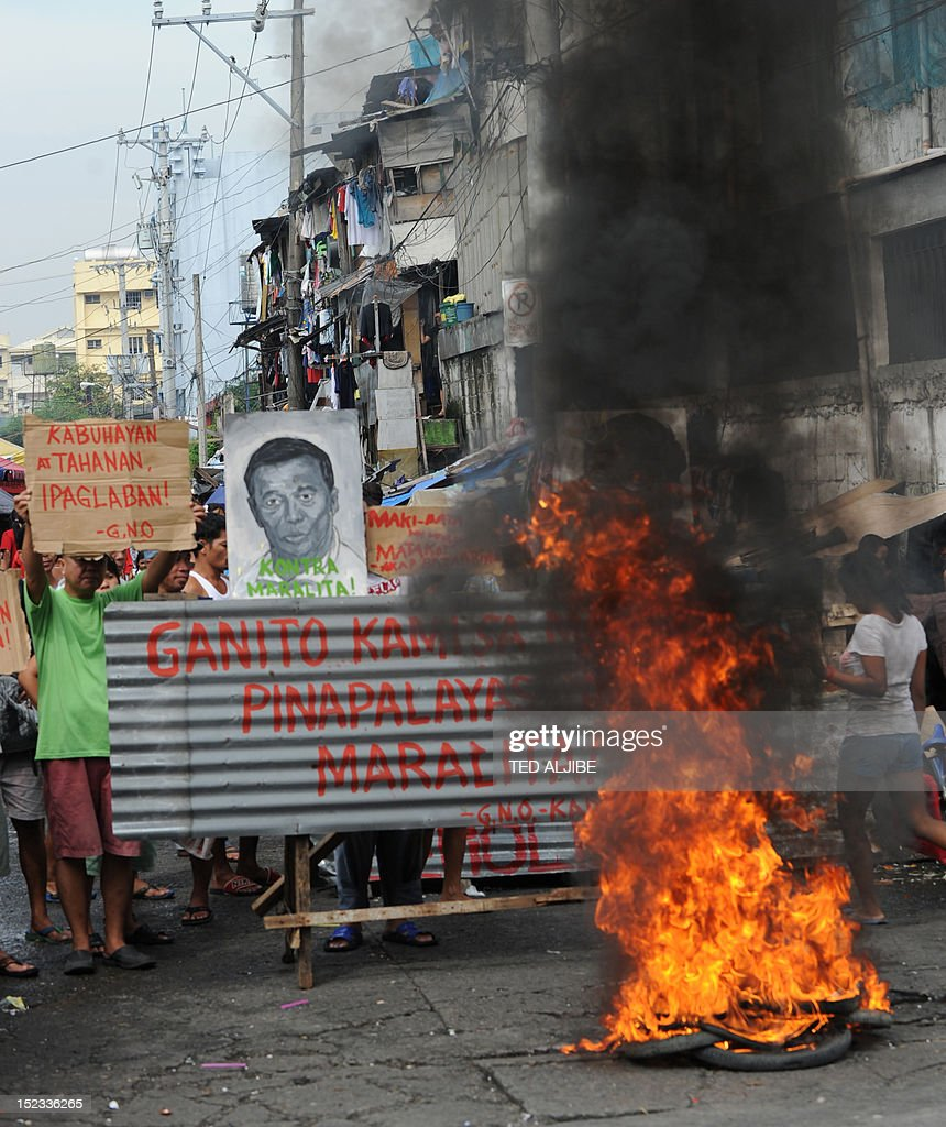 Informal settlers burn tyres next to portraits of Philippine President Benigno Aquino (R) and Vice-President Jejomar Binay, as they set up barricade at the entrance to their homes in anticipation of a demolition operation in the financial district of Manila on September 19, 2012. Around 250 informal settler families living on a 870,000 square metre lot will be affected by the demolition, to give way for the construction of a three-storey multi-purpose building for the city government. More than two million people in Metro Manila, or roughly one fifth of the sprawling city's population, live in shanty towns as so-called informal settlers.