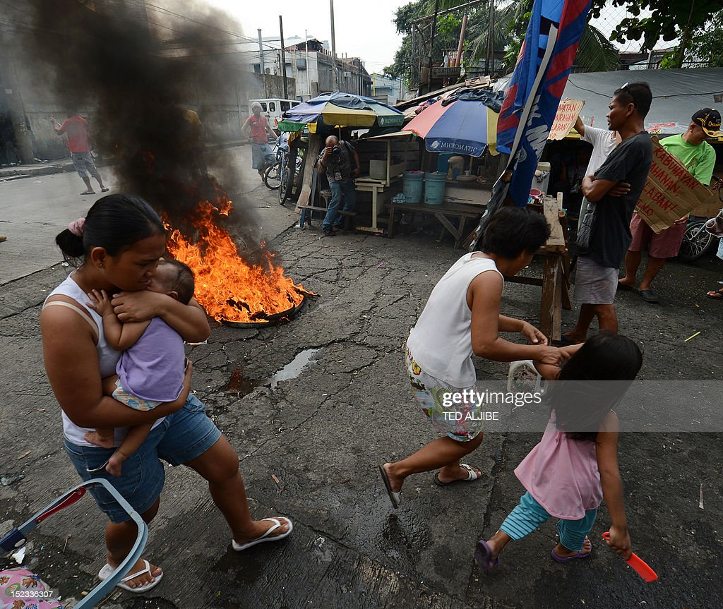 Informal settlers carrying their children run past burning tyres, while others guard the entrance to their homes in anticipation of a demolition operation in the financial district of Manila on September 19, 2012. Around 250 informal settler families living on a 870,000 square metre lot will be affected by the demolition, to give way for the construction of a three-storey multi-purpose building for the city government. More than two million people in Metro Manila, or roughly one fifth of the sprawling city's population, live in shanty towns as so-called informal settlers.