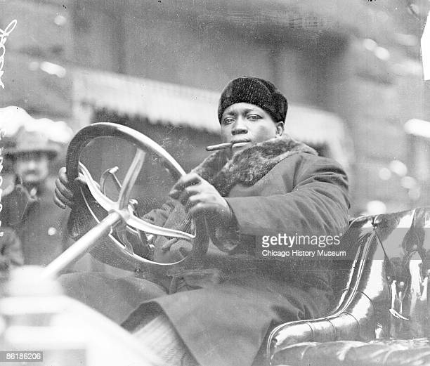 Informal threequarter length portrait of Jack Johnson an African American pugilist looking at the camera sitting in the driver's seat of an...