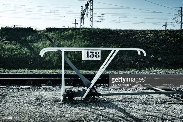 Information Sign On Railroad Track Against Sky