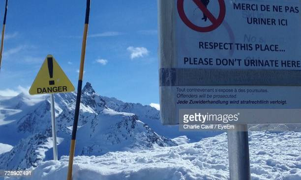 Information Sign On Snow Covered Mountains Against Sky