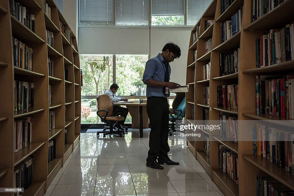 Infosys Ltd. employees browse reading material in the library at the company's campus in Electronics City in Bangalore, India, on Monday, Feb. 4, 2013. Infosys is India's No. 2 software exporter. Photographer: Sanjit Das/Bloomberg via Getty Images