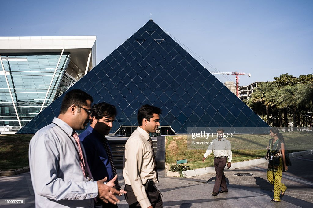 Infosys Ltd. employees walk past the K. Dinesh Communication Design Center at the company's campus in Electronics City in Bangalore, India, on Monday, Feb. 4, 2013. Infosys is India's No. 2 software exporter. Photographer: Sanjit Das/Bloomberg via Getty Images