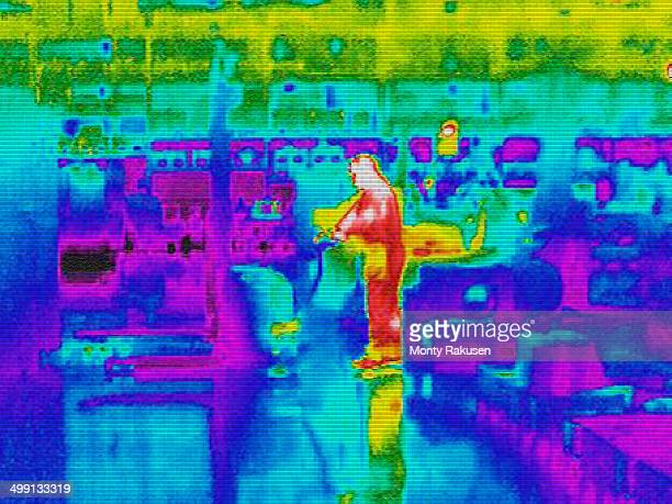 Infra red heat image of worker and heat loss at work station in factory