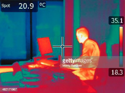 Infrared heat image of office worker sitting at desk