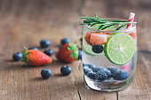 Infused water made from blueberry strawberry and lemon in sparkling mineral water look so freshness and healthy. Mixed fruit mojito on wood table with copy space. Summer refreshing drink concept.
