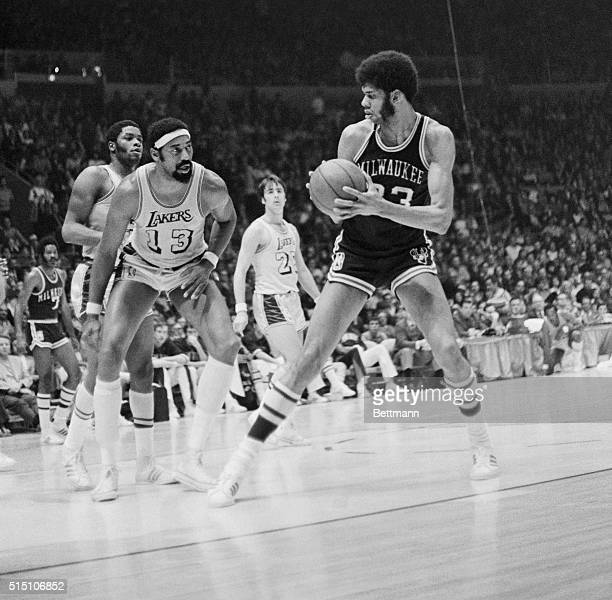 Two of basketball's giants stare at each other as Milwaukee Buck Lew Alcindor tries to decide if he should go over Los Angeles Laker Wilt Chamberlain...