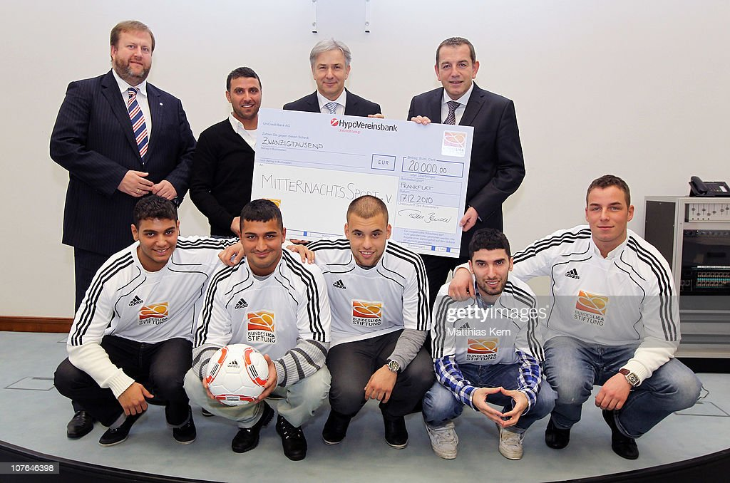 Ingo Schiller of Hertha BSC, Ismail Oener, Berlin Mayor Klaus Wowereit , Tom Bender of DFL and the team of the social project 'MitternachtsSport' (back, L-R) pose with a cheque at Rotes Rathaus on December 17, 2010 in Berlin, Germany. The DFL Foundation supports the social project 'MitternachtsSport'.