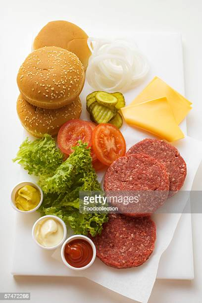 Ingredients for cheeseburgers on chopping board
