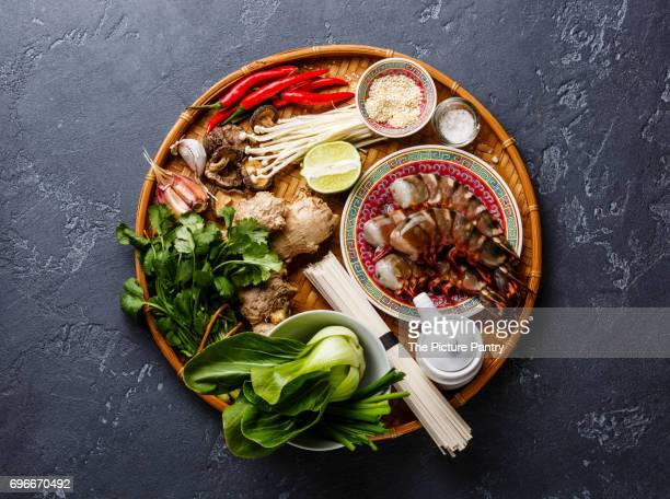 Ingredients for cooking Asian food with Tiger shrimps, udon noodles, mushrooms, greens, vegetables, spices