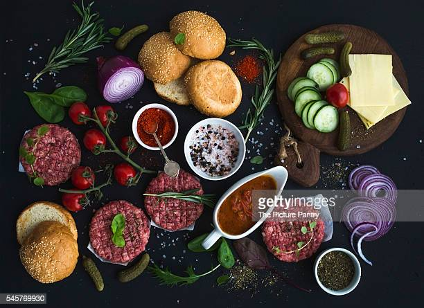 Ingredients for cooking burgers. Raw ground beef meat cutlets, buns, red onion, cherry tomatoes, greens, pickles, tomato sauce, cheese, herbs and spices over black background, top view.