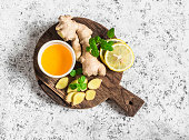 Ingredients for cooking detox drink - ginger, lemon, honey, mint. On a light background, top view