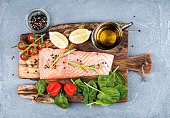 Ingredients for cooking healthy dinner. Raw salmon fillet, spinach, tomatoes, olive oil, lemon, peppers, rosemary and spices on a rustic wooden board over concrete textured grey background. Top view