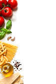 Top view of ingredients for cooking traditional Italian pasta placed at the left border of a vertical white background making a frame and leaving useful copy space for text and/or logo. The compositio