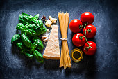 Top view of ingredients for cooking traditional Italian spaghetti making the colors of the Italian flag shot on dark bluish tint table. The horizontal composition includes spaghetti, olive oil, garlic
