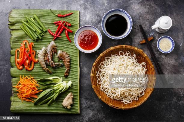Ingredients for cooking Udon noodles with Tiger shrimps, greens, vegetables, spices on banana leaf on dark background