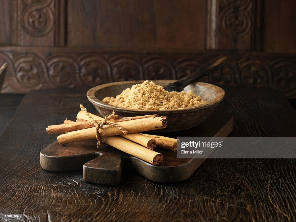 Ingredients for dry cure sugar glazed gammon joint. Cinnamon sticks tied with string and brown sugar in wooden bowl