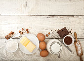 Ingredients for the preparation of bakery products: flour eggs butter milk chocolate cocoa nuts. Top view. Rustic style. White wooden background.